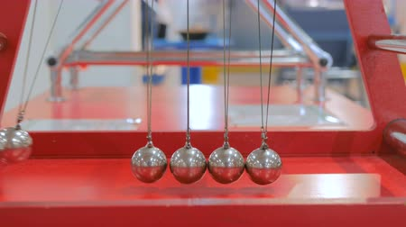 lendület : Interactive exposition in science museum. Demonstration of Newtons cradle work at technology museum. Science and physics concept