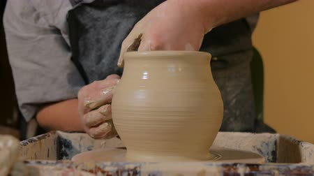 pitcher : Professional male potter shaping pot in pottery workshop, studio. Crafting, artwork and handmade concept