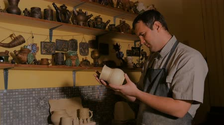 louça de barro : Professional male potter examining earthenware pot in pottery workshop, studio. Crafting, artwork and handmade concept