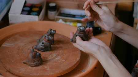 decorador : Professional woman potter, decorator painting ceramic souvenir penny whistle toy dog in pottery workshop, studio. Crafting, artwork and handmade concept