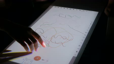 érintés : Woman using interactive touchscreen projector display for drawing at modern technology show. Future and entertainment concept