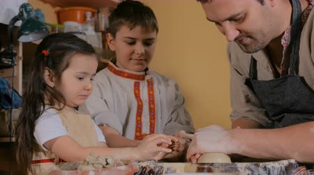 shaping : Pottery class and workshop: professional male potter working with children and showing how to make ceramic wares in pottery studio. Handmade, education and study concept Stock Footage
