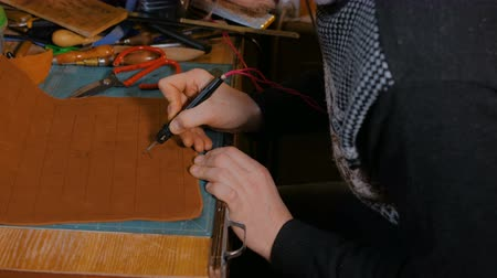 xadrez : Professional male skinner, tanner making decorative details on leather playing field for strategy board game -tafl with special pyrographic machine