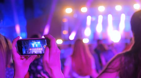 fire arms : Unrecognizable woman hands silhouette taking photo or recording video of live music concert with smartphone at night. Photography, entertainment and technology concept Stock Footage