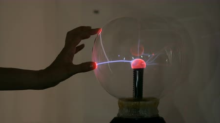 electrostatic : Interactive exposition in science museum. Woman touching plasma ball. Electricity and physics concept