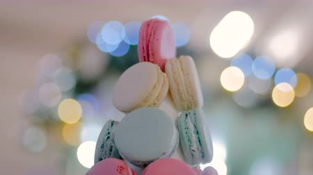 pyramida : Macaron tower - multicolored tasty french macaroons with Christmas bokeh garland light. French cuisine, candy, holiday, new year and food concept Dostupné videozáznamy