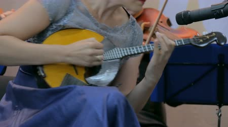 traditional instruments : Symphony concert - unrecognizable woman playing mandolin - close up shot. Music and culture concept