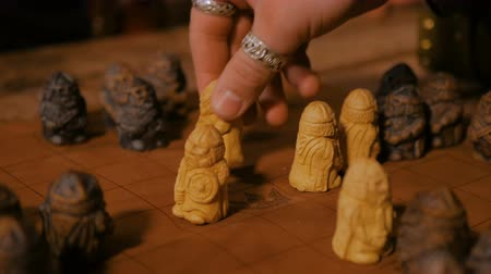 statuette : Game preparation - close up shot of man hand placing figures for medieval popular strategy board game - tafl. Folk, competition and traditional concept