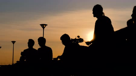 perkusja : Unrecognizable group of people silhouette playing ethnic percussion drum musical instruments on street at sunset. Street music and urban culture concept