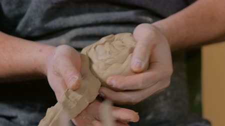 oleiro : Professional male potter kneads clay in pottery workshop, studio. Handwork, crafting and traditional arts concept