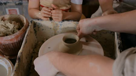 hrnčíř : Pottery class and workshop: professional male potter working with children and showing how to make ceramic wares in pottery studio. Handmade, education and study concept Dostupné videozáznamy