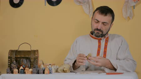 esculpir : Professional male potter in russian ethnic shirt making clay figure for medieval popular strategy board game - tafl. Handwork, crafting and traditional arts concept