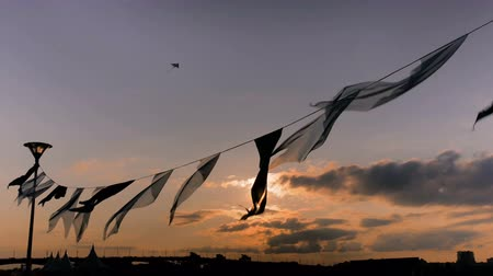 pipa : Decorative garland of satin flags silhouette waving in the wind at city street holiday, festival or carnival. Sunset light, sun lens flare. City festival concept Stock Footage