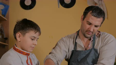 oleiro : Pottery class and workshop: professional male potter working with kid and showing how to make ceramic wares in pottery studio. Handmade, ethnic, education and study concept Stock Footage