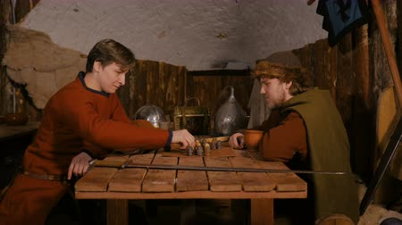 statuette : Two men in russian ethnic suit playing medieval popular strategy board game - tafl. Folk, competition and traditional concept