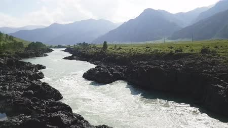 altay : Rapid current of Katun River in Altai Mountains. Summer time. Rocky coast. View from the bridge.