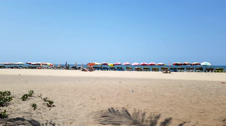 goa : Timelapse of seashore with sun beds. People go on the beach, open multi-colored umbrellas. Sunny summer hot day.