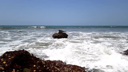 goa : Timelapse of stony coast of the Arabian Sea, Strong waves break against big rocks. Summer time.
